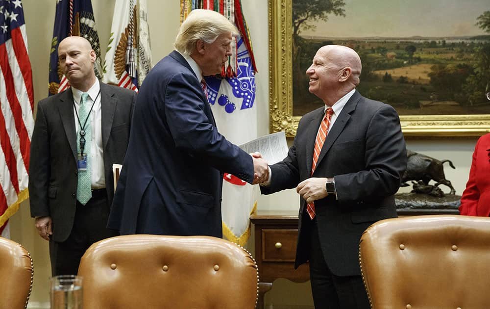President Donald Trump shakes hands with House Ways
