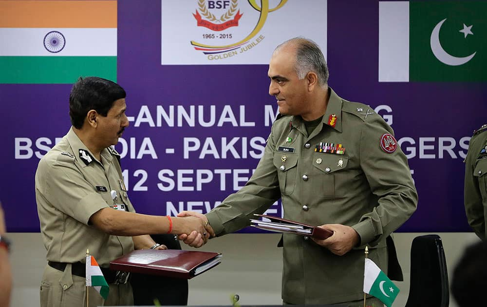 Border Security Force (BSF) Director General D.K. Pathak and Pakistani Rangers Director General (Punjab) Maj. Gen Umar Farooq Burki shake hands as they exchange copies of the joint accord at Indian Border Security Force (BSF) headquarters in New Delhi.