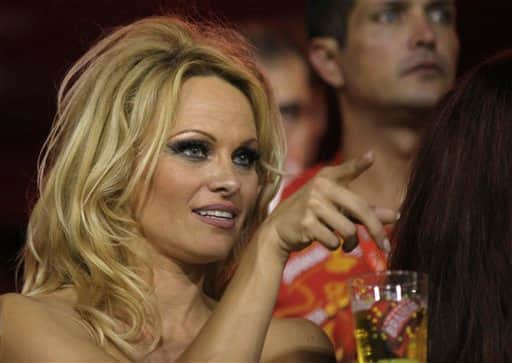Pamela Anderson gestures from the stands as she watches a carnival parade at the Sambadrome in Rio de Janeiro, Brazil.