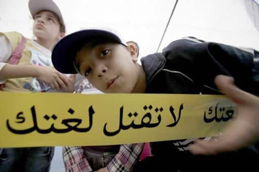 A Lebanese child poses behind a ribbon that reads