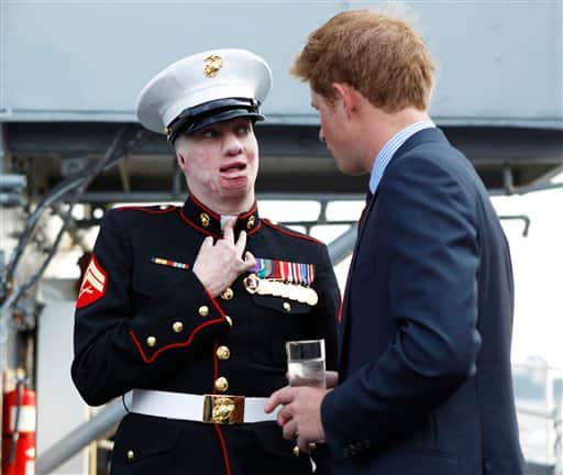 Britain`s Prince Harry, right, speaks with U.S. Marine veteran Aaron Mankin on the deck of the USS Intrepid during his visit to New York, Friday, June 25, 2010.