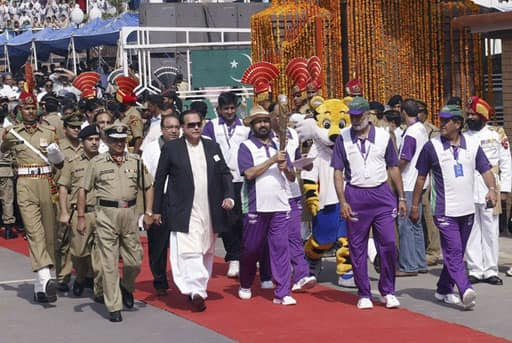 President of the Indian Olympic Association (IOA) Suresh Kalmadi holds the Queen`s Baton during the XIX Commonwealth Games Queen`s Baton Relay as Pakistani Punjab Governor Salman Taseer (in black coat) walk along with other officials at the India-Pakistan joint check-post at the Wagah border June 25, 2010. The Baton arrived in India from Pakistan on Friday. The Baton is carried through several Commonwealth countries in the run up to the Delhi 2010 Commonwealth Games in October 2010.
