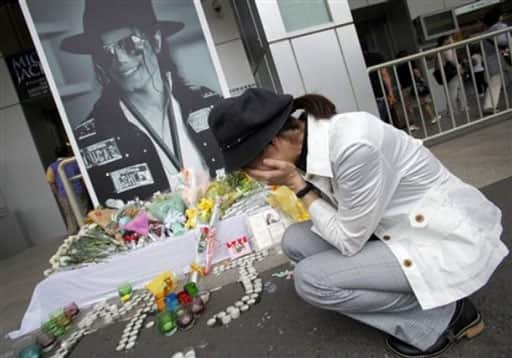 A woman cries in front of a portrait of late Michael Jackson displayed at a makeshift memorial place on his first death anniversary in Tokyo, Japan, Saturday, June 26, 2010.