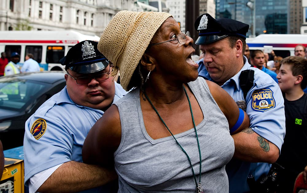 Police detain a woman who was swinging her cane at a demonstrator, not pictured, who was supporting Israel in its war with Hamas members in the Gaza Strip, during a rally at John F. Kennedy Plaza, also known as Love Park, in Philadelphia.