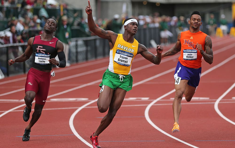 Baylor`s Trayvon Bromell, center, celebrates after winning the men`s 100 meters while Florida State`s Dentarius Locke, left, and Northwestern State`s Justin Walker, right, follow at the NCAA track and field championships, in Eugene, Ore.