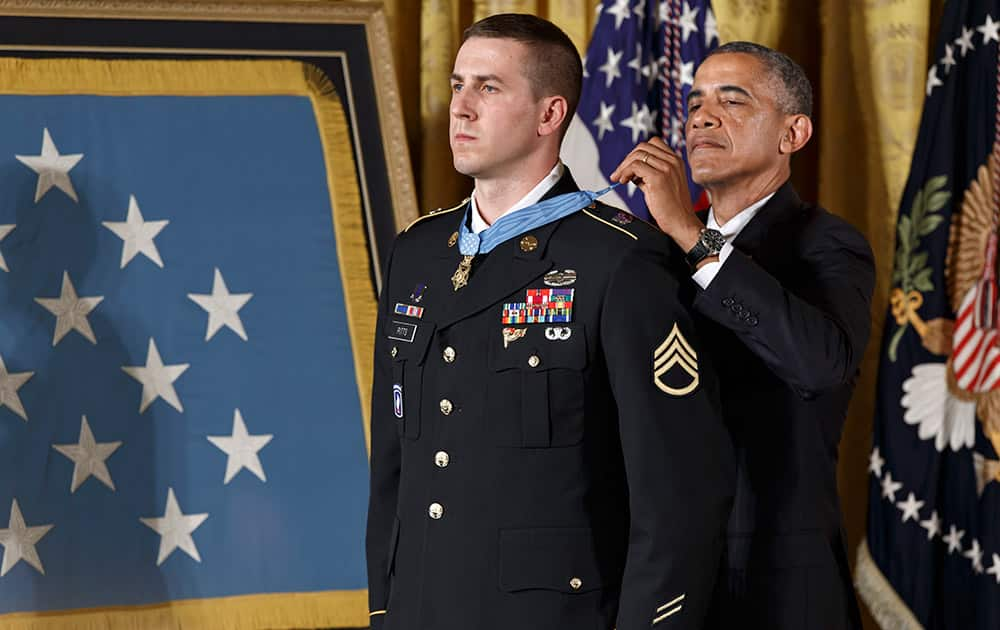 President Barack Obama bestows the Medal of Honor, the nation`s highest decoration for battlefield valor, to Ryan M. Pitts, 28, of Nashua, NH, a former Army staff sergeant who fought off enemy fighters during one of the bloodiest battles of the Afghanistan war despite his own critical injuries, in the East Room of the White House in Washington.