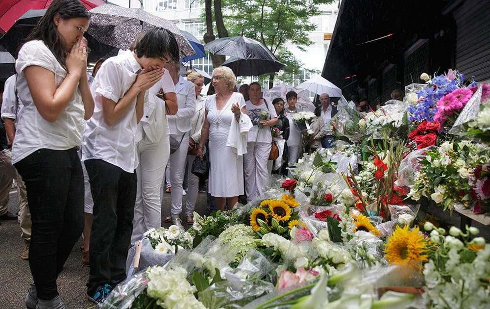 People react as they look at flowers placed in front of the Asian Glories restaurant, after a walk to commemorate victims of Flight 17 in Rotterdam.