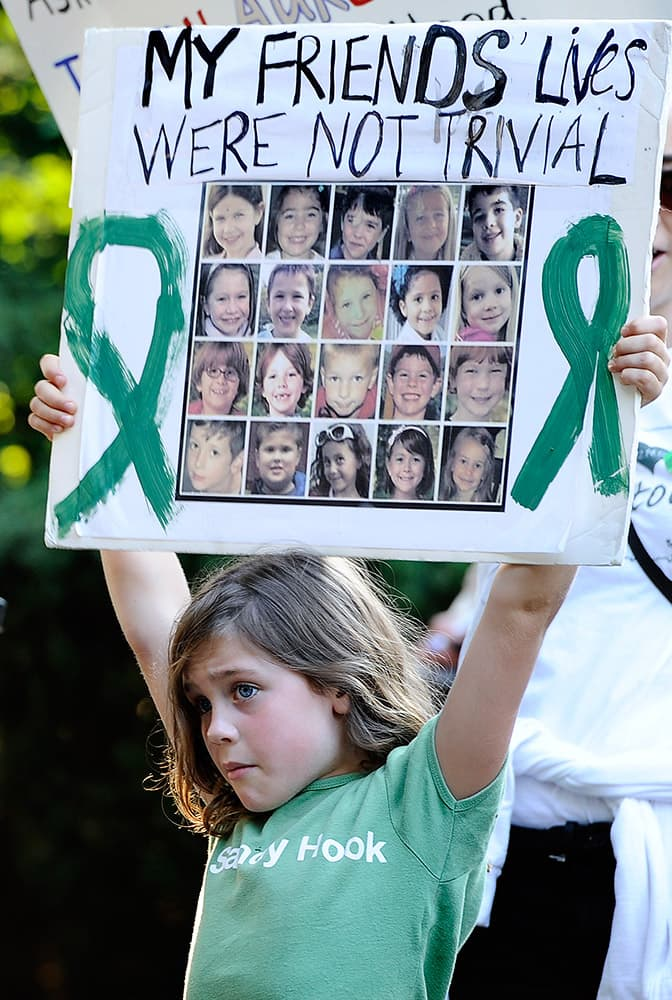 Marie Morosky, of Newtown, Conn. holds up a sign with images of the children killed in the Sandy Hook School shooting outside a fundraising event for Republican gubernatorial candidate Tom Foley with New Jersey Gov. Chris Christie at a private residence,  in Greenwich, Conn.