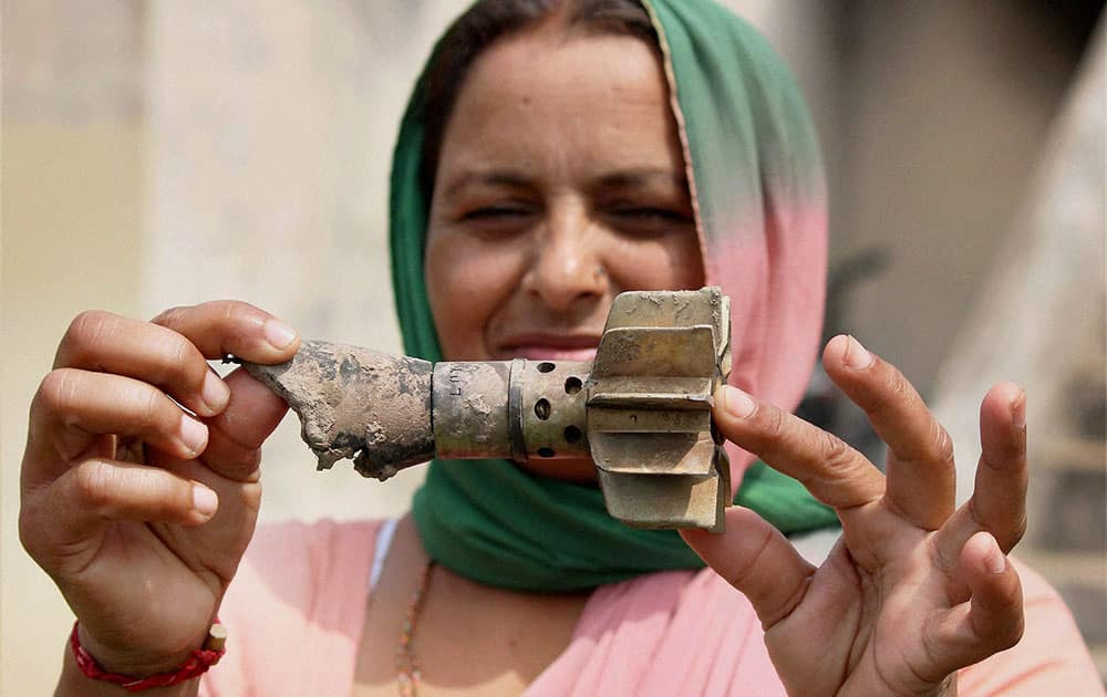 A woman shows a mortar shell recovered from a residential area after it was allegedly fired from Pakistan`s side in Gharna village at the India-Pakistan International border in RS Pura sector about 40 km from Jammu.