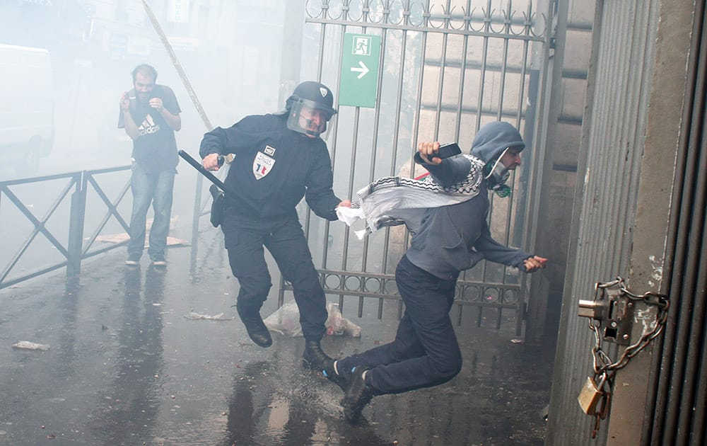 A riot police officer reacts with a pro-Palestinian demonstrator, during a demonstration in Paris.