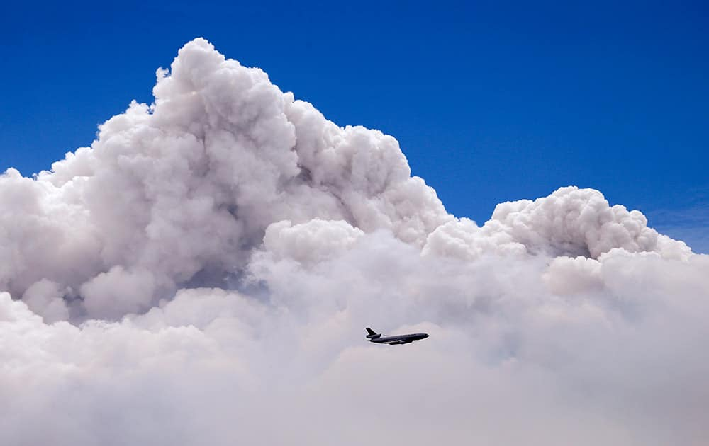 A DC-10 air tanker is dwarfed by the tip of a rising smoke cloud as the plane prepares to drop fire retardant over a wildfire near Carlton, Wash.