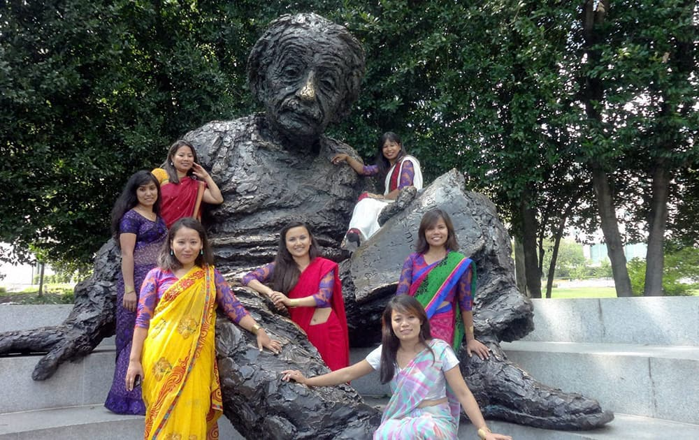 A group of seven women mountaineers from Nepal posing for a group picture at the statue of Albert Einstein outside the Foggy Bottom headquarters of the State Department in Washington.