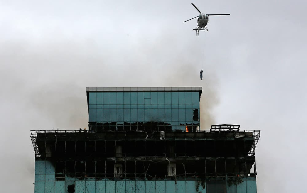 A Navy sailor descends from a helicopter to rescue a fireman trapped in a building on fire in Mumbai. One fireman was killed and several others injured in a fire that broke out in a commercial building Friday, according to a news agency.