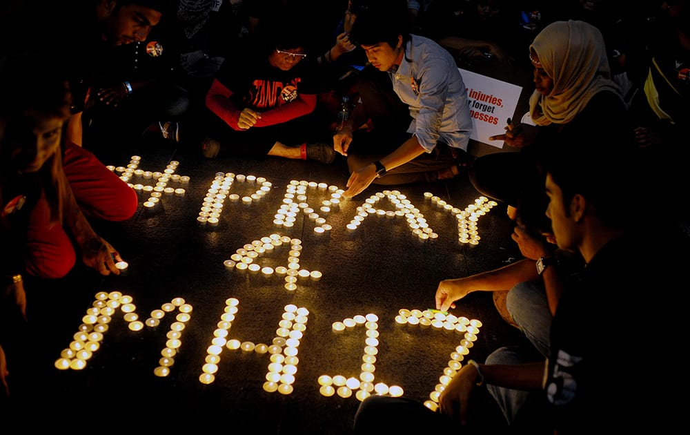 People arrange candles to offer prayers for the victims of the Malaysia Airlines Flight 17, at a shopping mall in Petaling Jaya, near Kuala Lumpur, Malaysia.