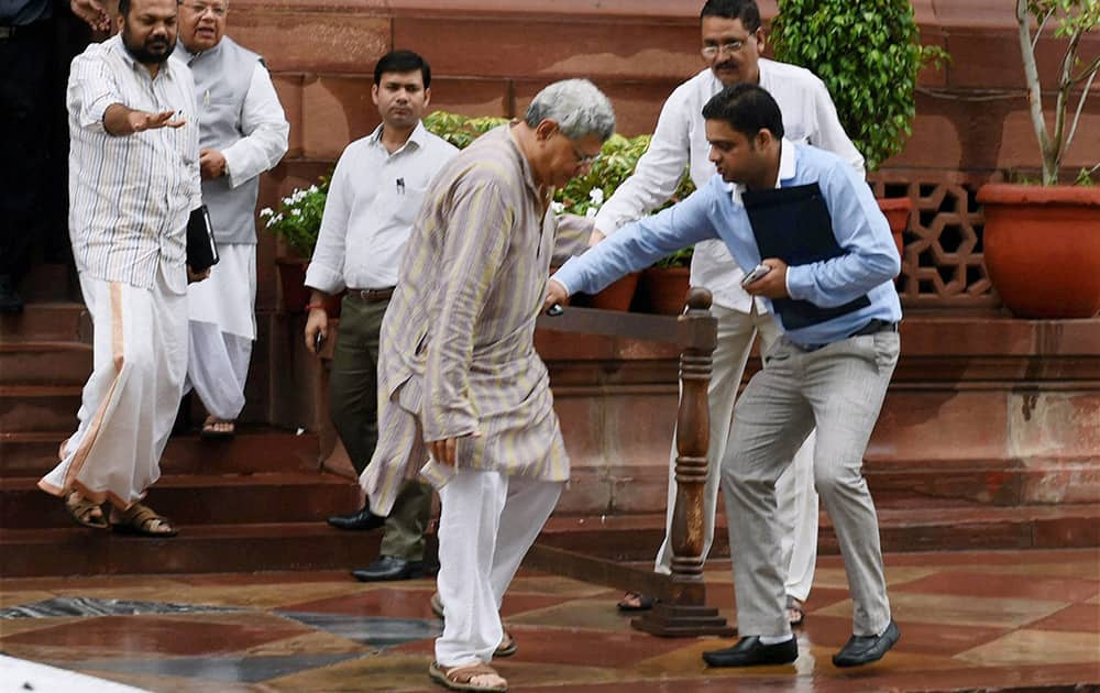 Left leader Sitaram Yechury is helped after he slips at Parliament House in New Delhi.