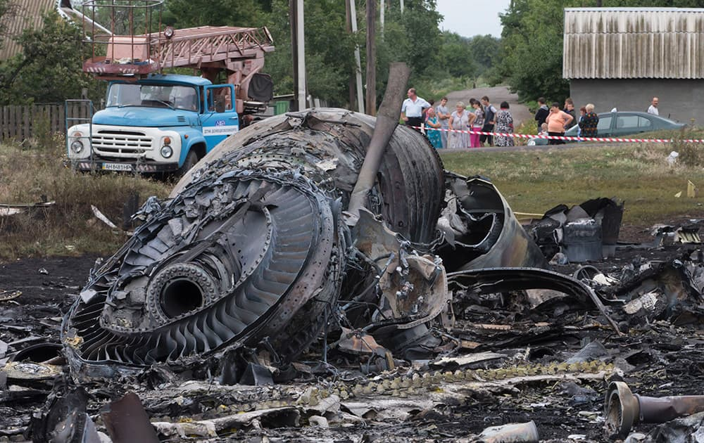 Local citizens, background, look at the site of a crashed Malaysia Airlines passenger plane near the village of Rozsypne, Ukraine, eastern Ukraine.