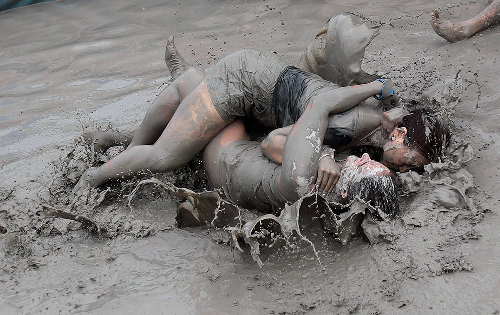 Women wrestle in a mud pool during the Boryeong Mud Festival at Daecheon Beach in Boryeong , South Korea. The 17th annual mud festival features mud wrestling and mud sliding.