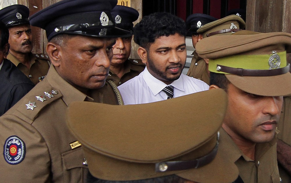 Police officials escort Sampath Vidanapathirana, a ruling party politician, convicted in a murder and rape case at the High Court complex in Colombo. A Sri Lankan court on Friday sentenced Vidanapathirana to 20 years in prison for killing a British tourist Khuram Sheikh and raping his Russian girlfriend more than two years ago.