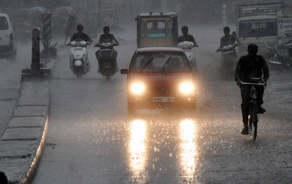 People move at a road amid heavy rains in Beawar.