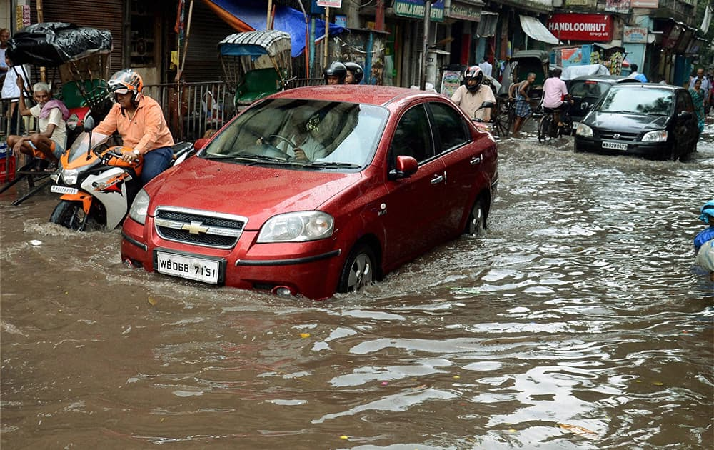 Vehicles move through a waterlogged road after heavy rains in Kolkata.