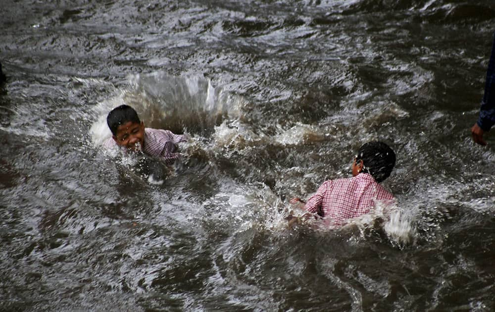 Children playing at a waterlogged road after heavy rains in Thane.