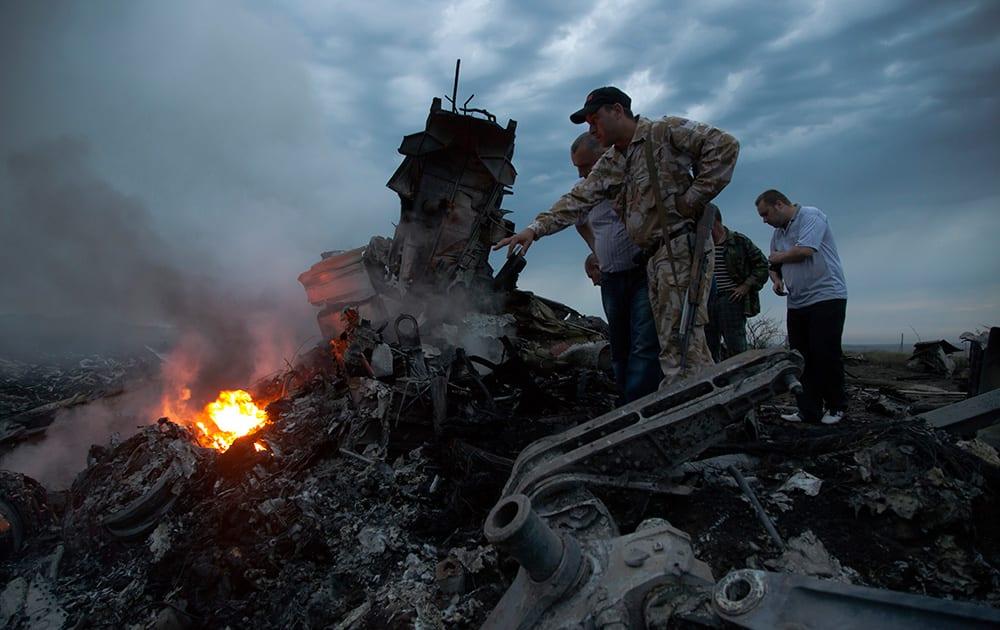 People inspect the crash site of a passenger plane near the village of Hrabove, Ukraine.