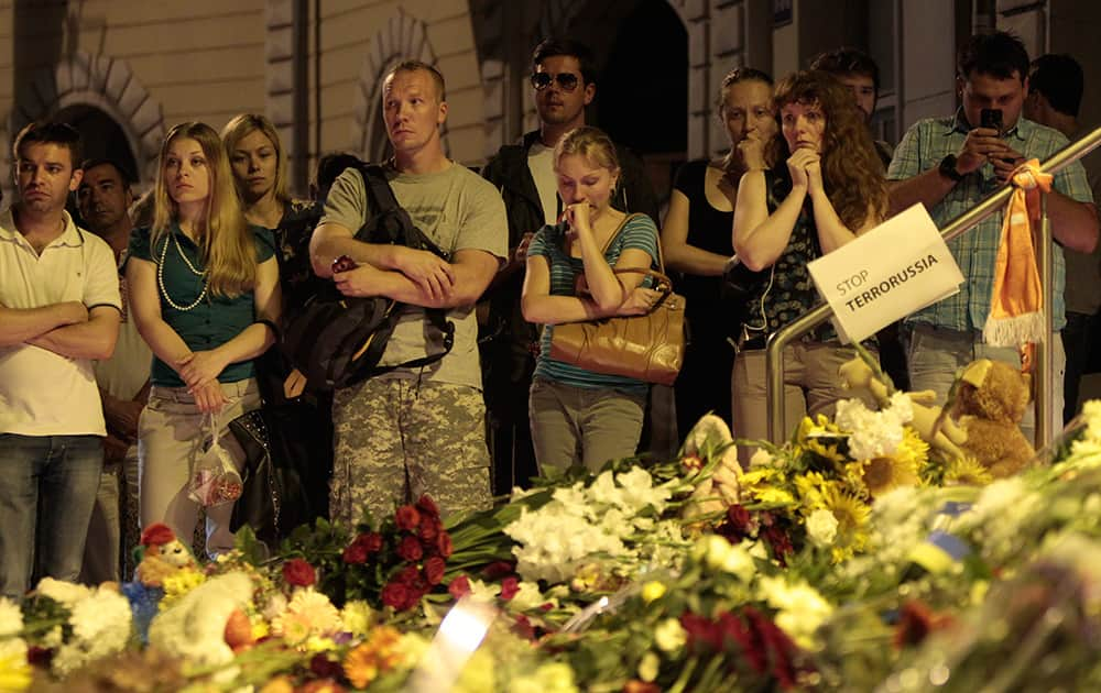 People stand near flower tributes placed outside the Dutch embassy to commemorate victims of Malaysia Airlines plane crash in Kiev, Ukraine.