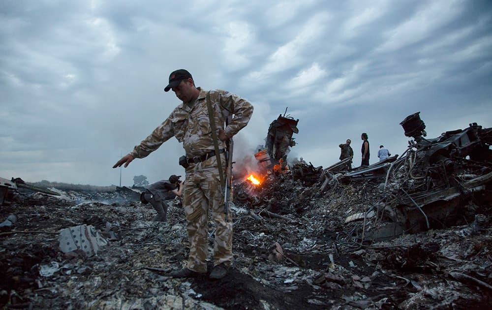 People walk amongst the debris at the crash site of a passenger plane near the village of Hrabove, Ukraine.