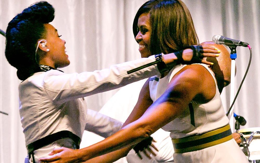 First Lady Michelle Obama, right, hugs six-time Grammy nominee singer Janelle Monae at the Grammy Museum's Jane Ortner Education Award Luncheon in Los Angeles.