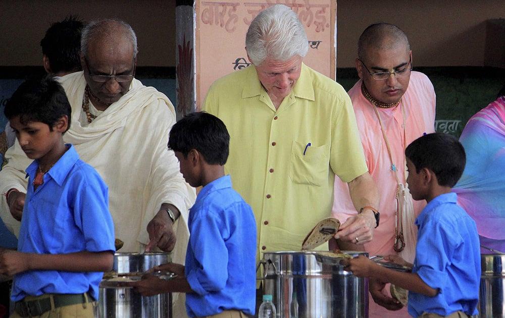 Former US President Bill Clinton serves food to students during a visit to `Akshaya Patra` kitchen in Jaipur.