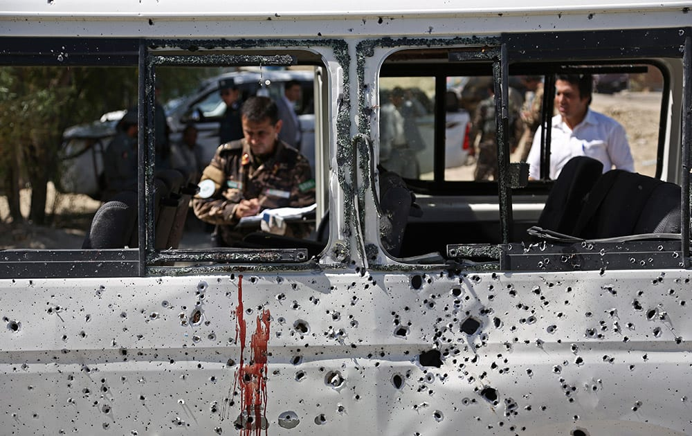 Afghan security personnel investigate a damaged minivan which was hit by a remote controlled bomb on the outskirts of Kabul, Afghanistan.
