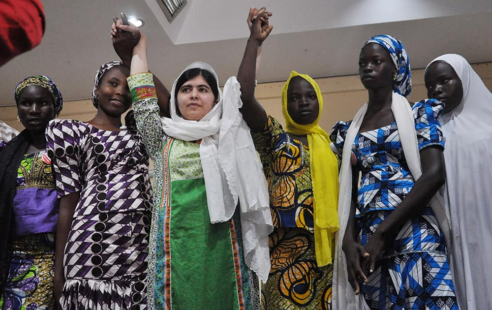 Pakistani activist Malala Yousafzai, centre, raises her hands with some of the escaped kidnapped school girls of government secondary school Chibok during a news confrence, in Abuja, Nigeria.