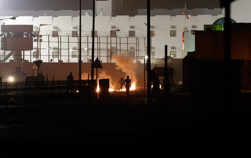 Bahraini anti-government protesters clash with riot police firing tear gas after protesters attacked a municipal building turned police station with petrol bombs in the western village of Karzakan, Bahrain.