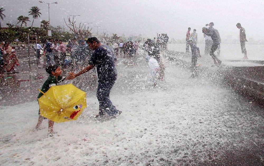 People enjoy high tide at Marine drive in Mumbai.