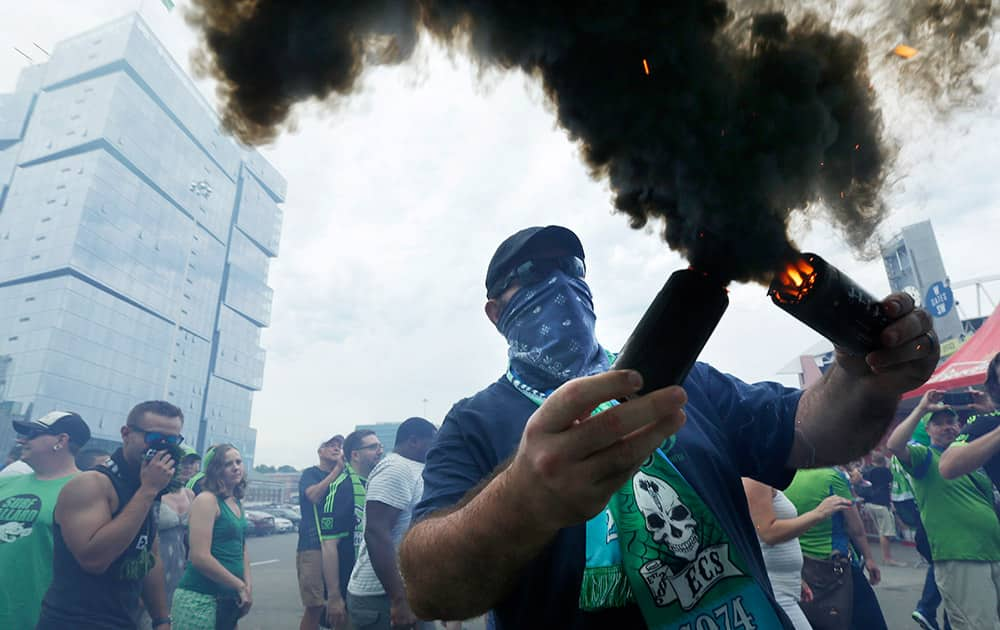 A Seattle Sounders supporter burns smoke devices during the traditional `March to the Match` before an MLS soccer match between Seattle Sounders FC and the Portland Timbers, in Seattle.