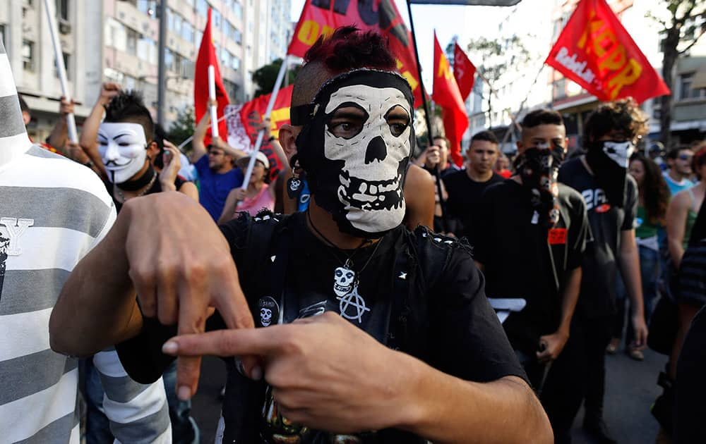 A masked demonstrator signals an anarchy sign during an Anti-World Cup protest near Maracana stadium where the final World Cup game is taking place in Rio de Janeiro, Brazil.