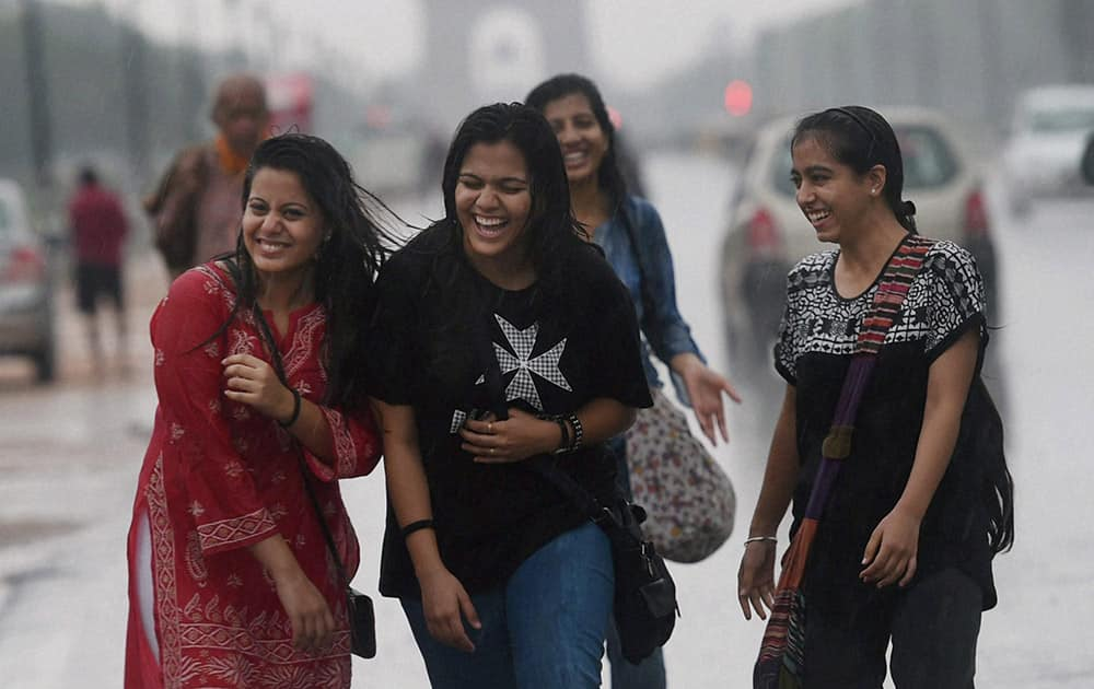 A group of girls revel in the rain at Rajpath in New Delhi.