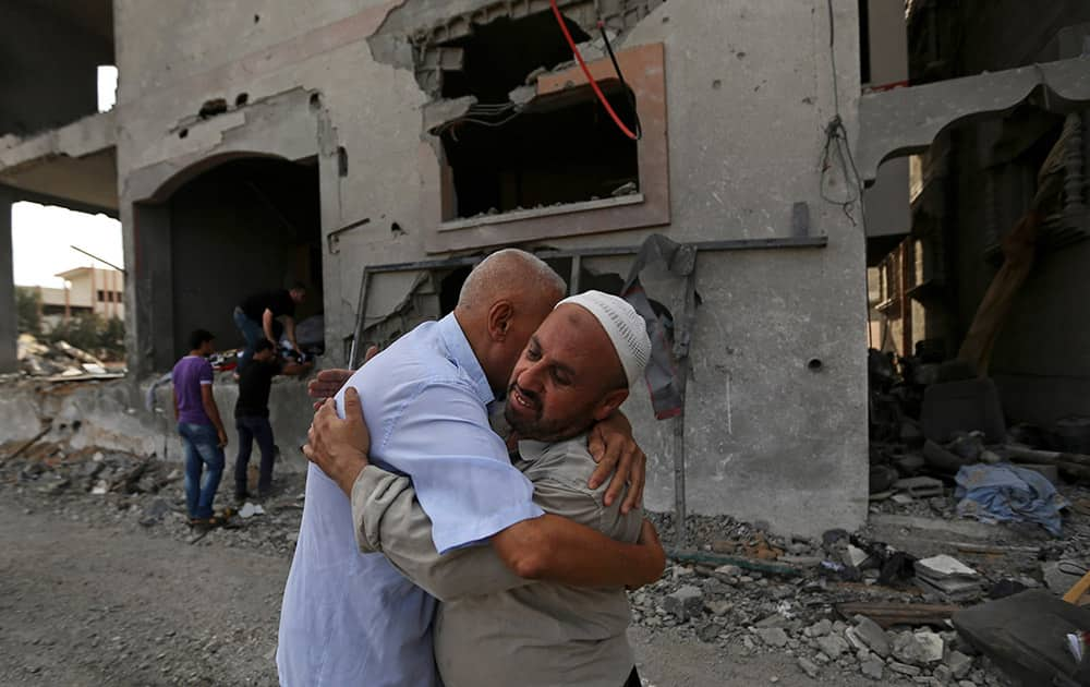 Palestinians give greetings in front of the damaged house of Gaza`s police chief Taysir al-Batsh after it was hit by an Israeli missile strike in Gaza City.