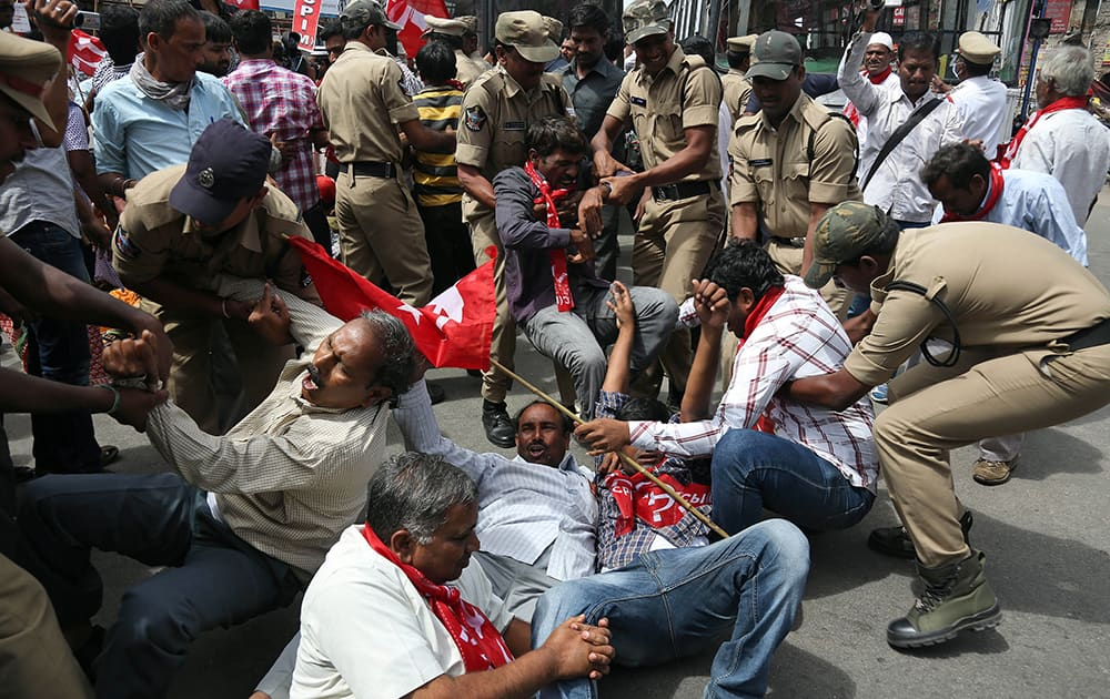 Indian policemen detain activists of left parties and other political parties during a protest against the ordinance on Polavaram project in Hyderabad.