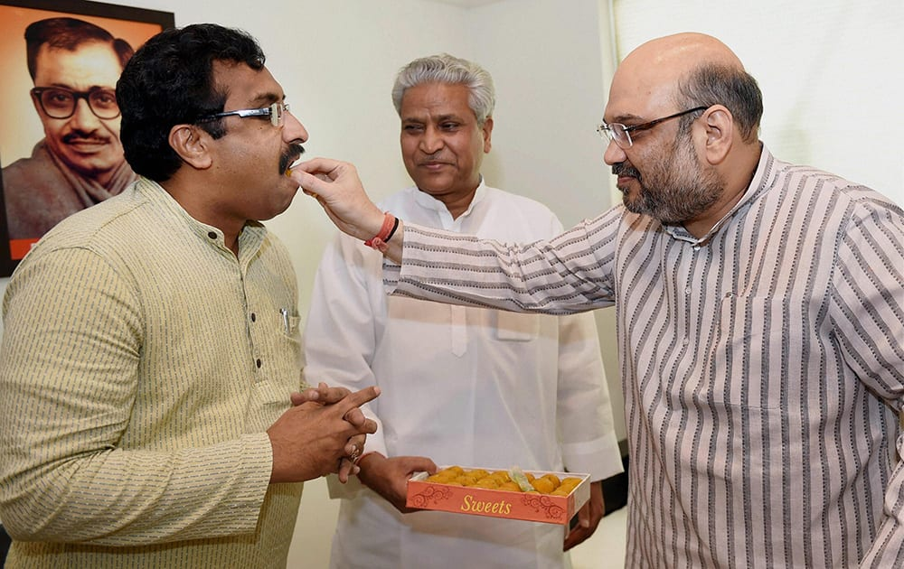 New BJP President Amit Shah offers sweets to the RSS spokesman Ram Madha after he joined the party at party headquarters in New Delhi.