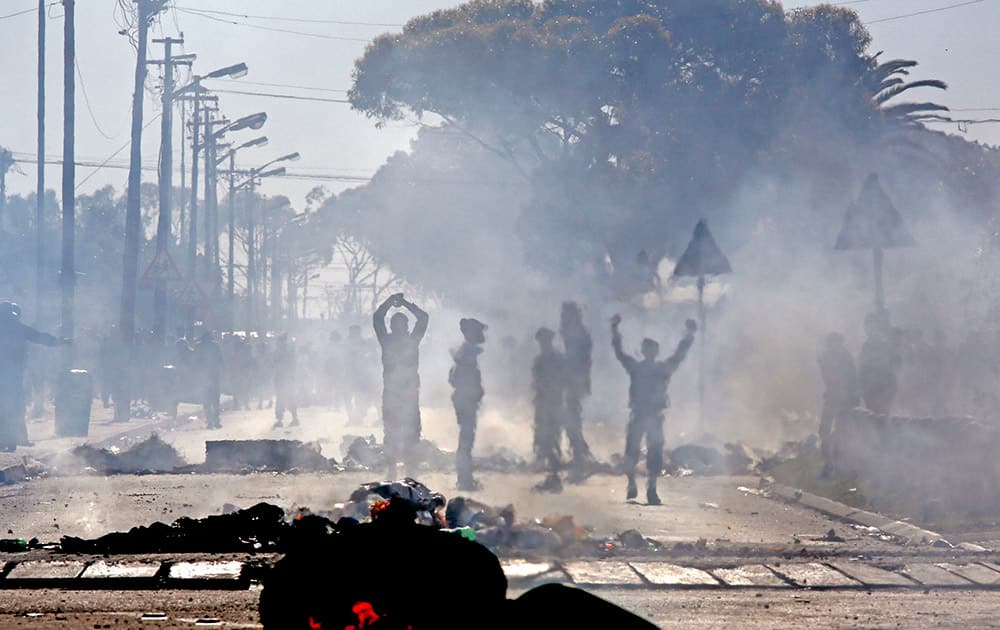 An electric pole and rubbish bins burns in the foreground, as Langa township residents protest, on the outskirts of the city of Cape Town, South Africa.