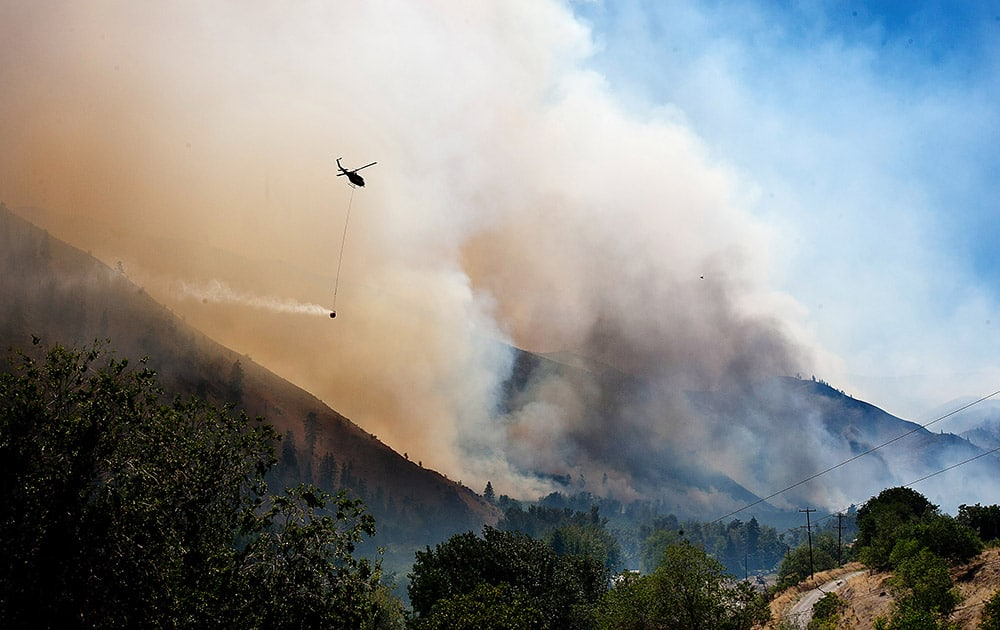 As smoke and fire blow through the lower Entiat Valley near Entiat, Wash., on Wednesday afternoon, a helicopter with a bucket of water flies to the fire to drop its load.