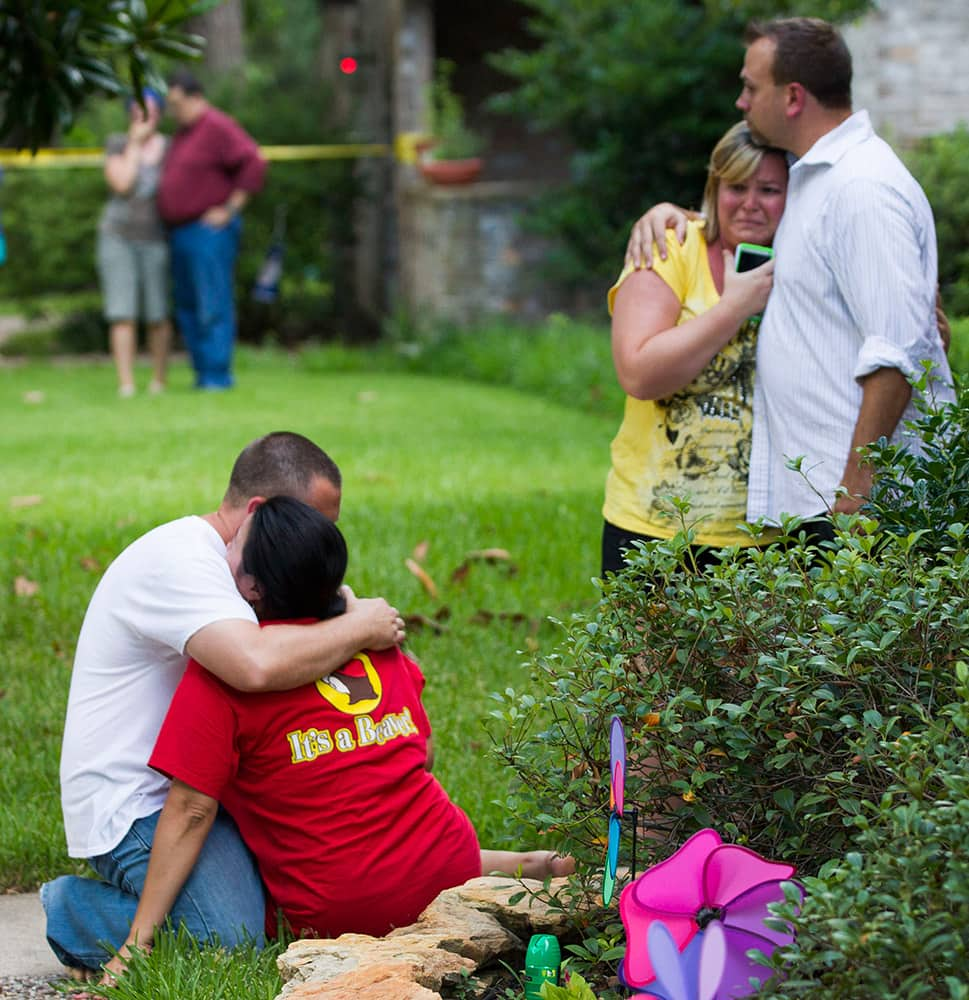 Neighbors embrace each other following a shooting in Spring, Texas.
