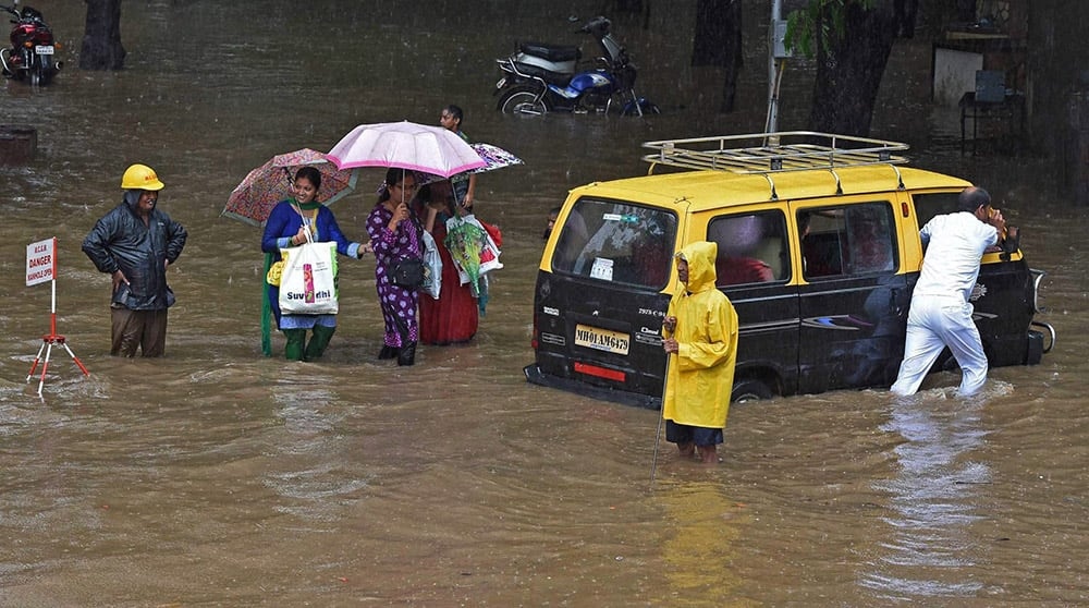 People wade through a waterlogged street after heavy rains in Mumbai.