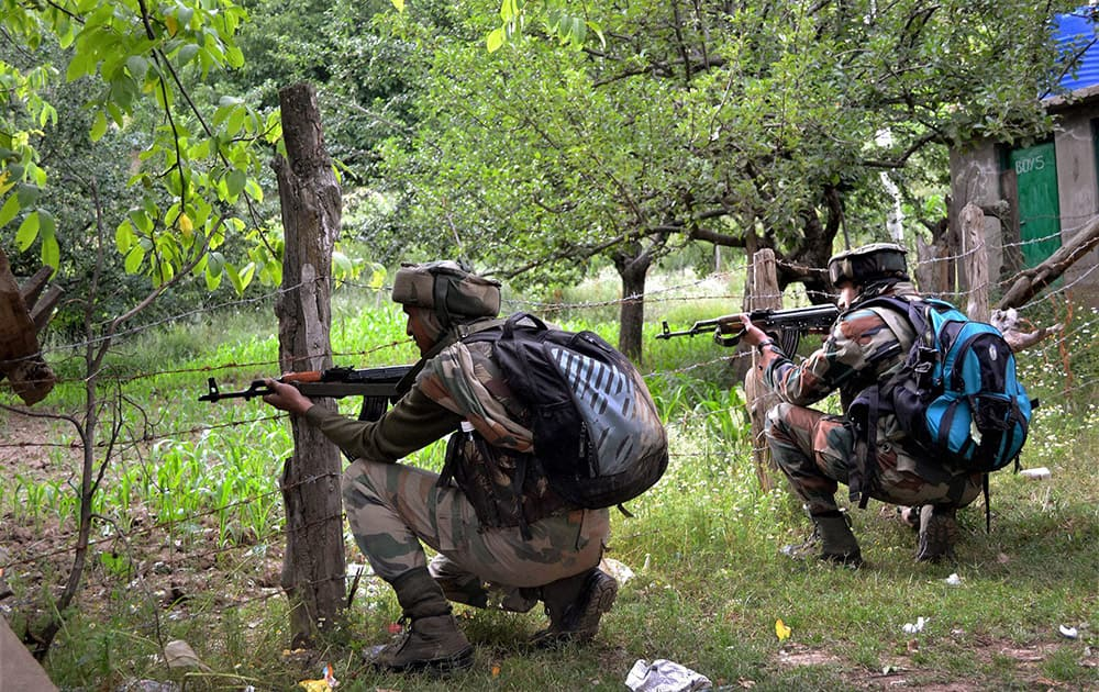 Army personnel takes position during an encounter with militants at Hamlapati village in Handwara.