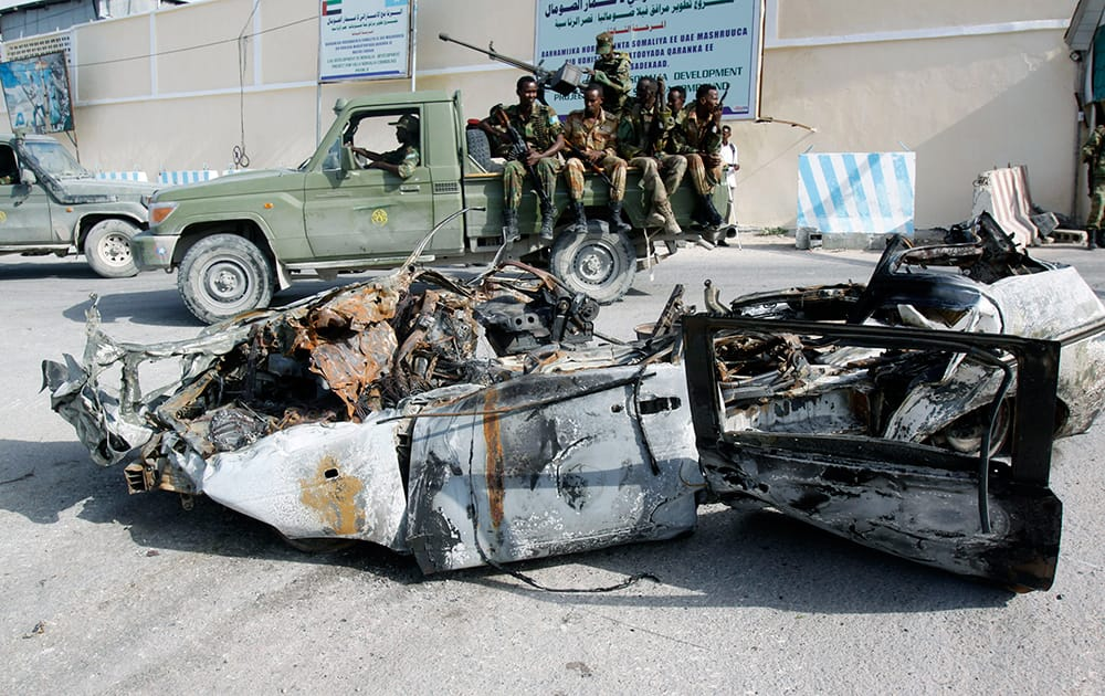 Somali soldiers sit on a pickup truck near the wreckage of a car bomb that was detonated at the main gate of the presidential palace in Mogadishu, Somalia.