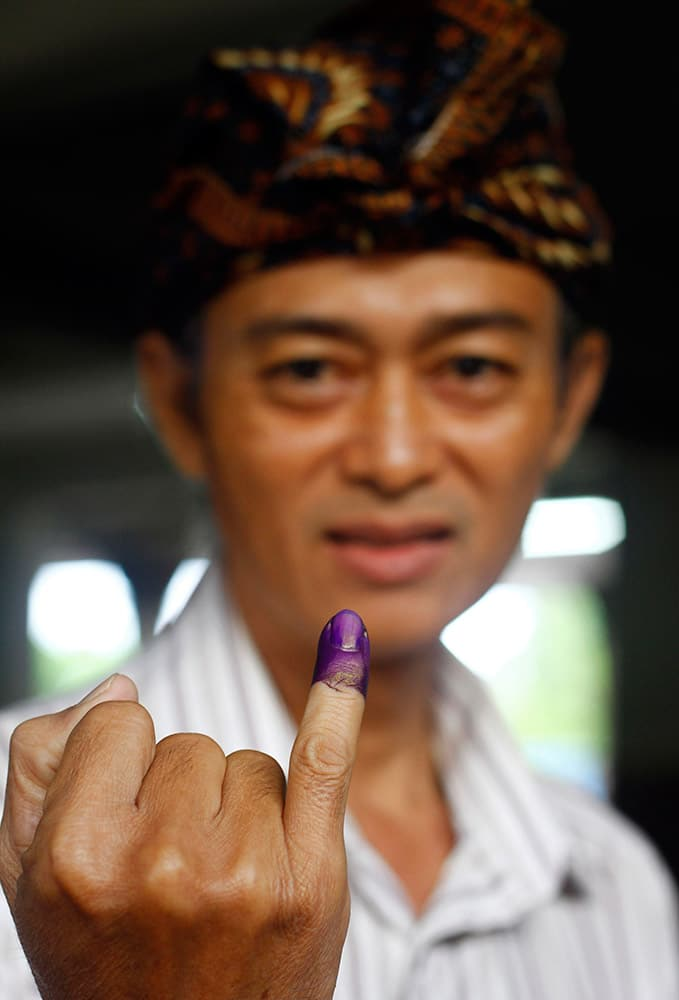 A voter shows off his finger marked with indelible ink after casting his ballot in the presidential election in Bali, Indonesia.