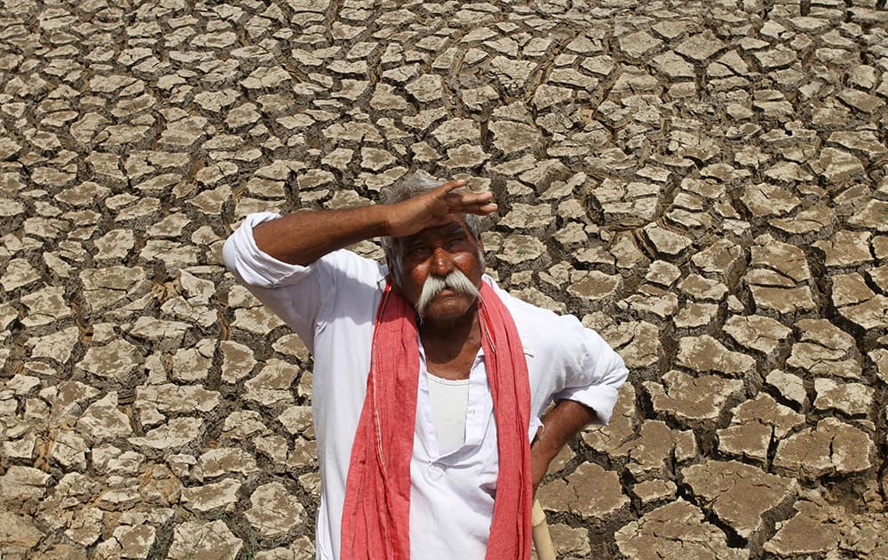 A farmer looks skyward as he stands on a dried bed of a water body on the outskirts of Ahmadabad. The western Indian state of Gujarat is facing a severe deficit in monsoon rain, according to news reports.