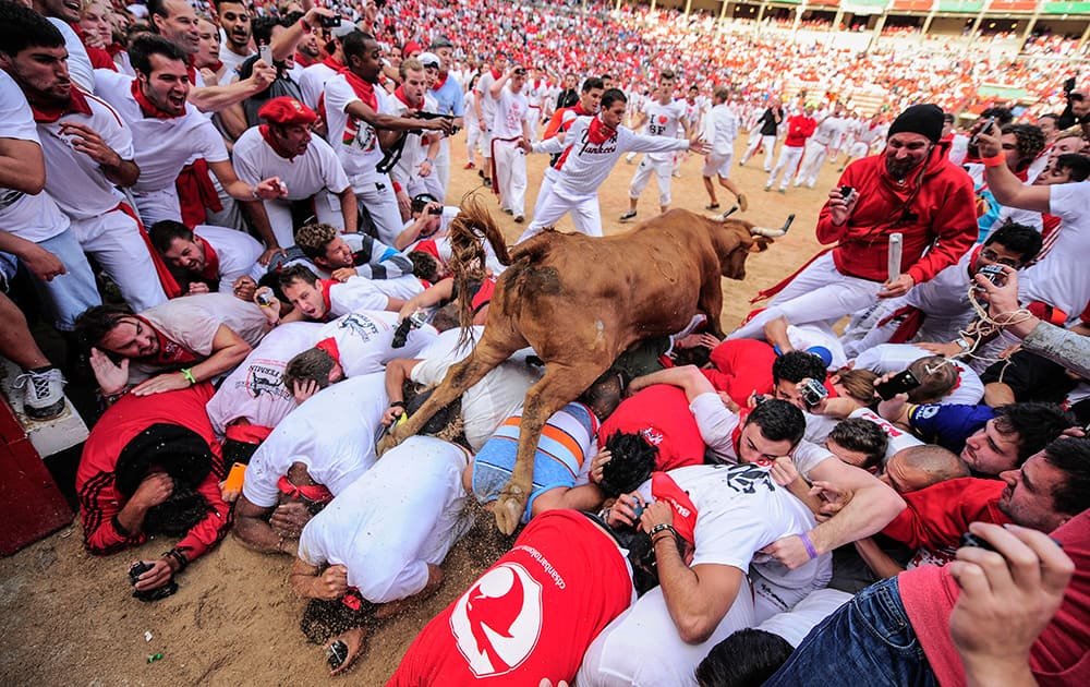 A cow jumps over revelers who wait for the animal on the bull ring, at the San Fermin festival, in Pamplona, Spain.