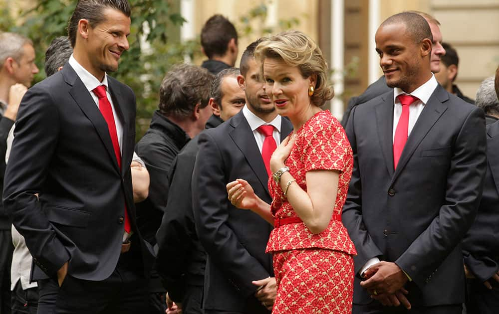Belgian Queen Mathilde , centre, talks with players of the Belgian national soccer team, Daniel Van Buyten, left, and team captain Vincent Kompany, right, at an event held after the team`s return from Brazil, at the Royal Palace in Brussels.
